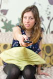 Brunette girl with a remote control. Sitting on a sofa Royalty Free Stock Image