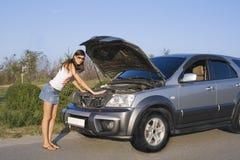 Brunette girl repairing the car royalty free stock photo