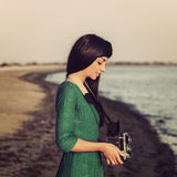 Brunette girl with retro camera by the sea Stock Images
