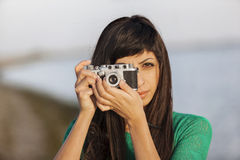 Brunette girl with retro camera by the sea Royalty Free Stock Images