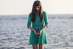 Brunette girl with retro camera by the sea Stock Photography