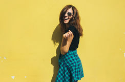 Brunette girl in rock black style, standing against yellow wall outdoors in the city street Royalty Free Stock Photo
