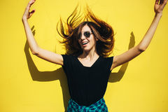 Brunette girl in rock black style, standing against yellow wall outdoors in the city street Stock Photo