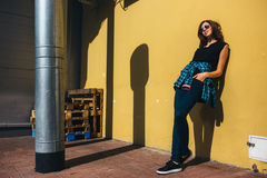 Brunette girl in rock black style, standing against yellow wall outdoors in the city street Stock Photos