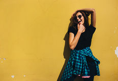 Brunette girl in rock black style, standing against yellow wall outdoors in the city street Royalty Free Stock Image