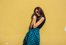 Brunette girl in rock black style, standing against yellow wall outdoors in the city street Royalty Free Stock Photos