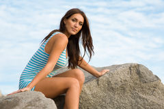 Brunette girl on a rock by the sea Royalty Free Stock Photo