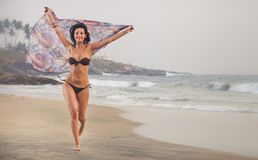 Brunette girl run on the beach Royalty Free Stock Images