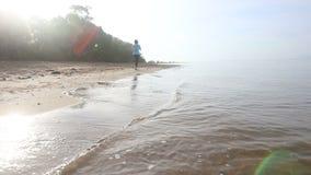 Brunette girl runs along water at backlight of sunrise stock video