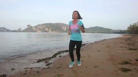 Brunette girl runs on beach against cliffs stock footage