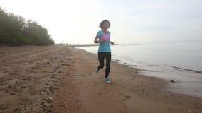 Brunette girl runs on beach at dawn stock video footage