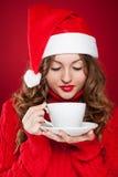 Brunette girl in Santa Clause hat holding white mug Royalty Free Stock Image