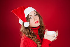 Brunette girl in Santa Clause hat holding white mug Royalty Free Stock Photos
