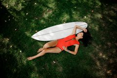 Brunette girl lying near her wakeboard on the grass royalty free stock photography