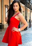Brunette girl in sexy red dress posing alone in the street. Royalty Free Stock Images