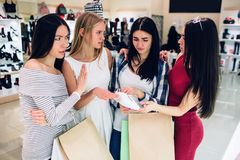 Brunette girl in shirt is holding one of the white crosses. She doubts to buy it. Her friend is giving advises to her royalty free stock photos