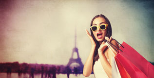 Brunette girl with shopping bags. On Parisian background royalty free stock photos