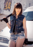 Brunette girl in short denim shorts with a bat royalty free stock photography
