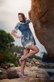 brunette girl in short frock high-heel shoes stands under rock Stock Images