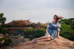 Brunette girl in short grey frock sits on rock against villas Stock Image