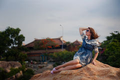 Brunette girl in short grey frock sits on rock against villas Royalty Free Stock Photography
