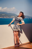Brunette girl in short grey frock smiles by wall against sea Royalty Free Stock Photography