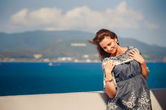 Brunette girl in short grey frock smiles by wall against sea Stock Photo