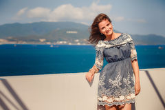 Brunette girl in short grey frock smiles by wall against sea Royalty Free Stock Photo