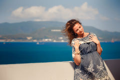 Brunette girl in short grey frock smiles by wall against sea Stock Photography
