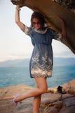Brunette girl in short grey frock stands under rock against sea Stock Photos