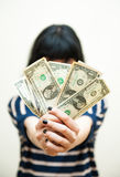 Brunette girl showing  money in hands selective focus. Brunette girl showing  money in hands with selective focus on white background Stock Image