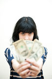 Brunette girl showing out of focus money in hands. On white background Royalty Free Stock Image