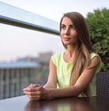 Brunette girl sitting. On the balcony of cafe Royalty Free Stock Photography