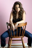 Brunette girl sitting on chair. Beautiful young gir sitting in a chair Royalty Free Stock Image
