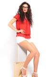 Brunette girl sitting on a chair with her hands on her waist whi Stock Photos