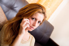 Brunette girl sitting on the ground telephoning Royalty Free Stock Photography