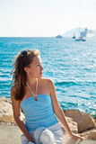 Brunette girl sitting on the rocky coast near clear azure sea. Stock Image