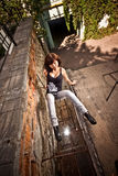 Brunette girl sitting on street against grungy background Royalty Free Stock Image