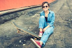 Brunette girl with skateboard sitting, smiling at camera, wearing jeans and modern outfit. Instagram filter, modern concept of hea royalty free stock photo