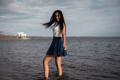 Brunette girl in a skirt standing in the water with her hair down. against the background of concrete and hydroelectric power. stock photo
