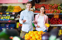 Brunette girl and smiling boyfriend buying citruses Royalty Free Stock Images