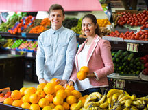 Brunette girl and smiling boyfriend buying citruses Royalty Free Stock Image