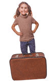 Brunette girl smiling child standing next to suitcase for travel Stock Photos