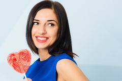 Brunette girl smiling, holding heart shaped red candy. Saint Valentine`s Day concept. Beautiful cheerful brunette girl dressed in blue smiling, holding heart royalty free stock photo