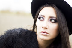 Brunette girl with smokey eyes. Outdoor fashion portrait of elegant brunette girl with smokey eyes. Dressed in coat and black hat Stock Images