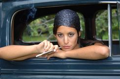 Sensual woman smoking in an old car. Brunette girl smoking in a car