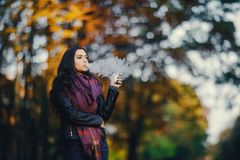 Brunette girl is smoking an e-cigarette. In the park drung autumn stock photo