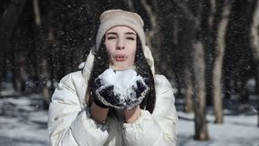 A brunette girl in a snowy forest in a white down jacket and in winter gloves in her hands holds the snow and blows it. To the camera. Winter vacation stock video footage