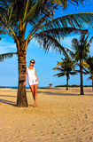 Brunette girl standing on the lonely sand beach Stock Photos