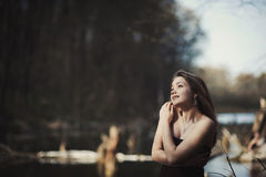 Brunette girl stands by the tree near the water Royalty Free Stock Images